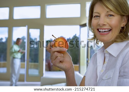 Mature woman eating apple at home, senior man in background, focus on woman, smiling, side view, portrait - stock photo
