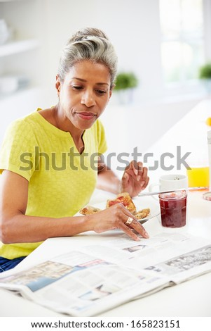 Mature Woman Eating Breakfast And Reading Newspaper - stock photo