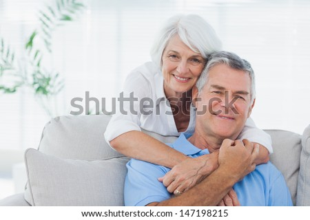 Mature woman embracing husband sitting on the couch - stock photo