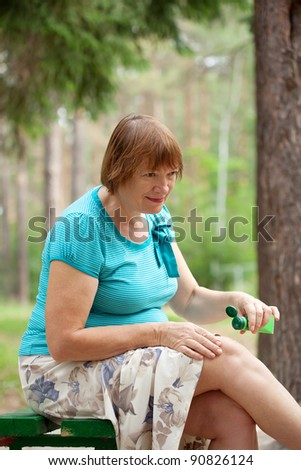 Mature woman embrocating jel in  injury knee - stock photo