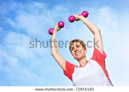 Mature woman exercising outdoors in the fresh air, raising dumbbells above her head - stock photo