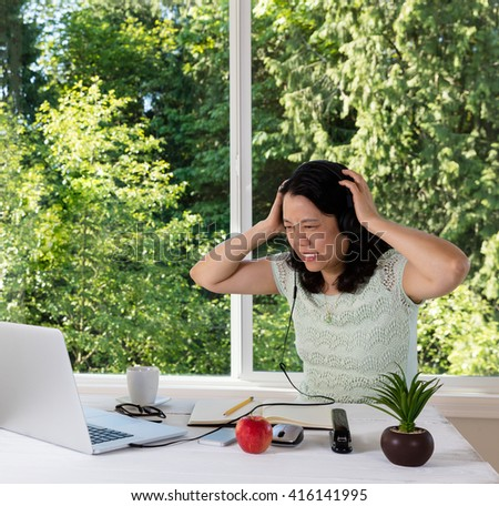 Mature woman, expressing frustration, working at home.