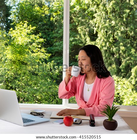 Mature woman, eyes closed, enjoying her morning coffee while working from home in front of large daylight window.  - stock photo