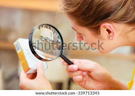 Mature woman female inspecting testing butter food label with magnifying glass. - stock photo