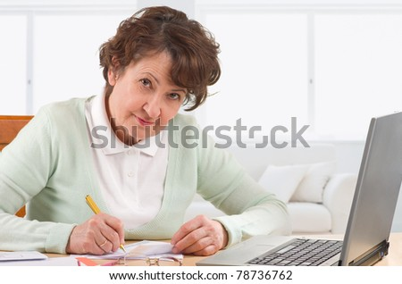Mature woman fill finance invoice at home - stock photo