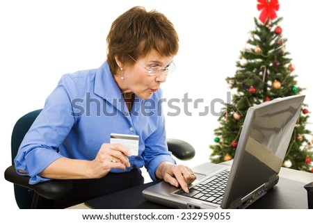 Mature woman finds a bargain shopping online for Christmas presents.  Isolated on white.   - stock photo