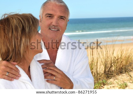 Mature woman gazing lovingly at her partner in the sand dunes - stock photo