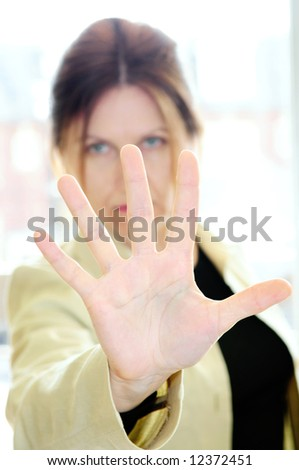 Mature woman gesturing stop with palm of her hand - stock photo