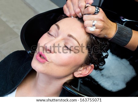 mature woman getting head massage and hair washed in salon
