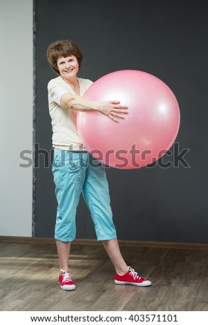 Mature woman gymnastics. Woman with fitness ball. Old woman is smiling in the studio. Mellow woman do her exercises and smile.  - stock photo