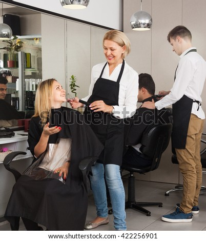 Mature woman hairdresser cuts hair of blonde girl at salon