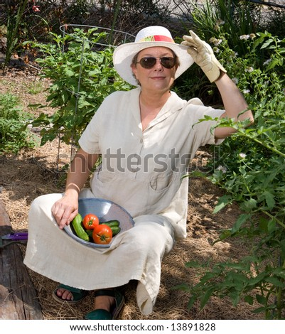 Mature woman harvesting tomatoes and cucumbers in her summer garden. - stock photo