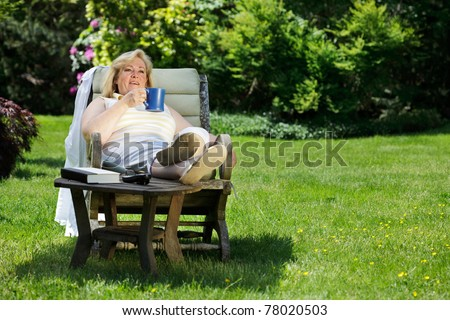 Mature woman has a coffee/tea break outside on a sunny Spring morning - stock photo