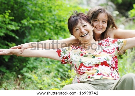Mature woman has happy time with her daughter in nature - stock photo