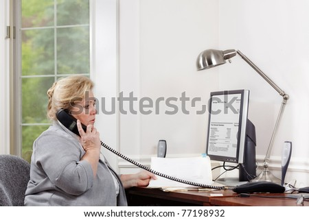 Mature woman having a phone discussion in a home office. Clipping path for monitor screen - stock photo