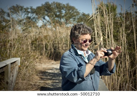 Mature woman having fun with her small digital camera on vacation, hiking and birdwatching in a national park. - stock photo