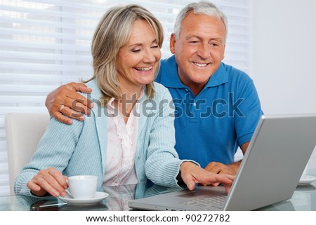 Mature woman having tea and browsing internet with her husband on laptop - stock photo