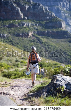 Mature woman hiking on mountain trail, carrying rucksack, using hiking pole, rear view - stock photo