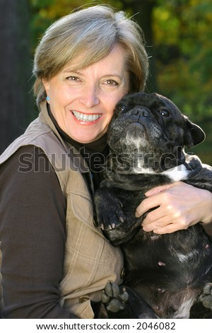Mature woman holding a bulldog. Focus on woman's face. - stock photo