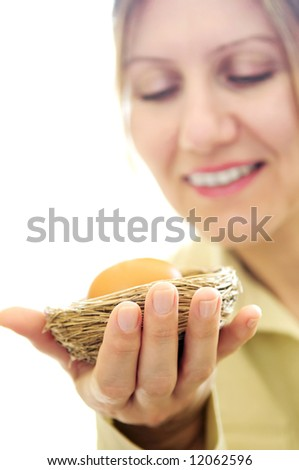 Mature woman holding a nest with an egg - investment concept - stock photo