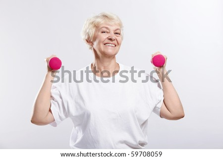 Mature woman holding dumbbells on a white background