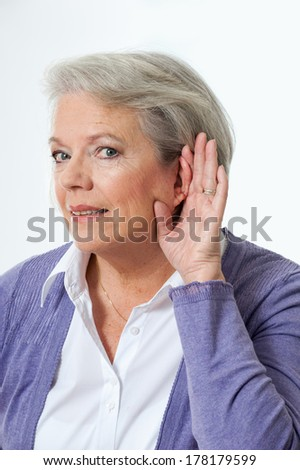 Mature woman holding hand to ear - stock photo