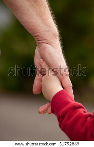 Mature woman holding hands walking with with young child