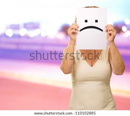 mature woman holding sad smiley, outdoor - stock photo
