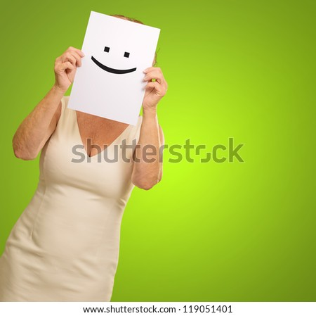 mature woman holding smile sign isolated on green background - stock photo