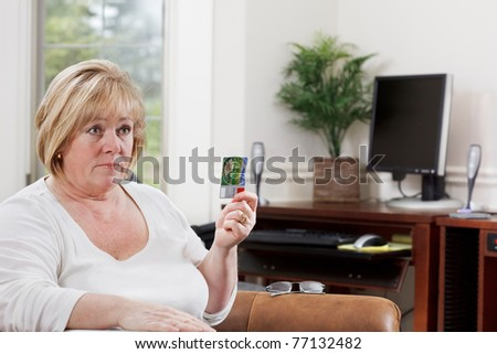 Mature woman holds a credit card and stares intently