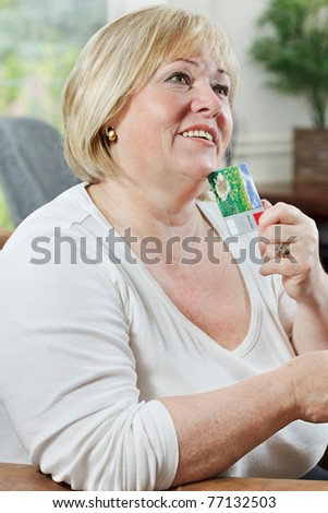 Mature woman holds credit card and dreams about what she's going to buy - stock photo