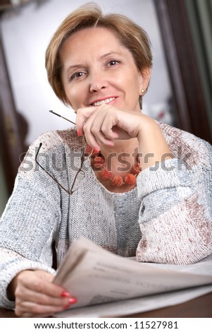 Mature woman holds newspaper and smiles - stock photo
