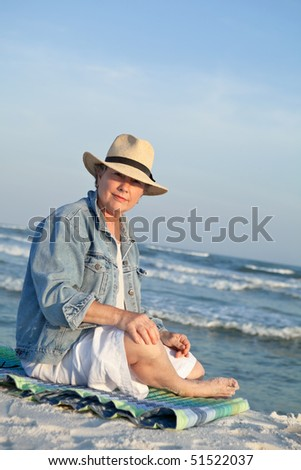 Mature woman in a Panama hat, seated at the beach at sunset.
