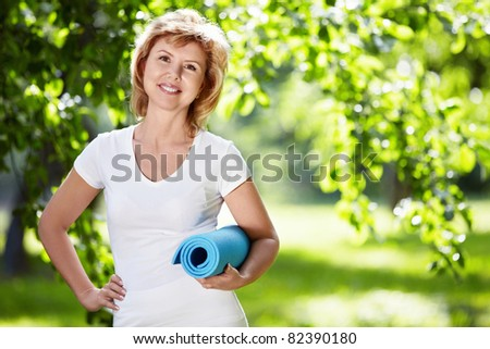 Mature woman in a park with a gymnastic mat - stock photo