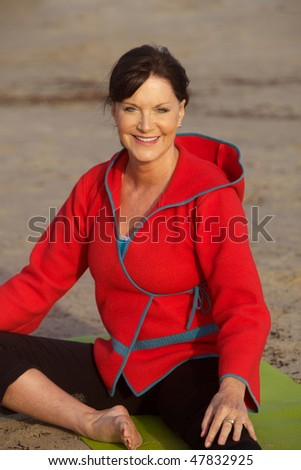 Mature Woman in a red jacket and a yoga mat - stock photo