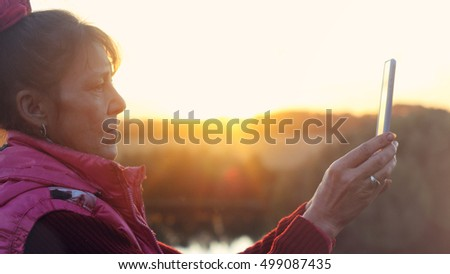 Mature woman in age using a phone in the mountains during sunset