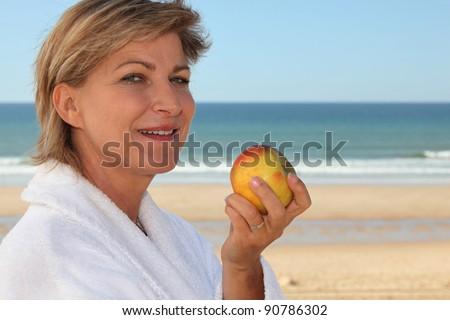 Mature woman in bathrobe - stock photo