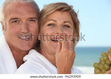 mature woman in bathrobe at spa resort eating grapes with husband - stock photo