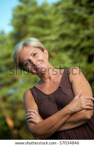 Mature woman in brown dress smiling - stock photo