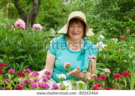 Mature woman in carnation plant at garden