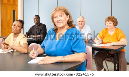 Mature woman in college, among a group of other adult students.   Banner orientation. - stock photo