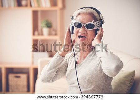 Mature woman in funny sunglasses  and headphones singing a song - stock photo