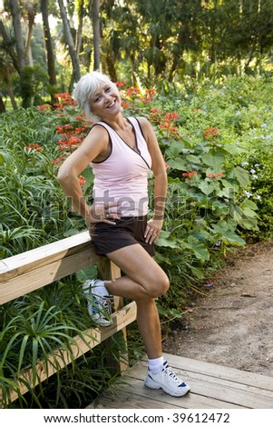 Mature woman in her 50s in workout clothes and running shoes standing on wooden bridge in park - stock photo