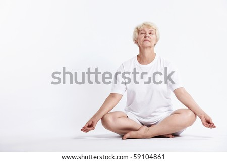 Mature woman in lotus position on a white background - stock photo