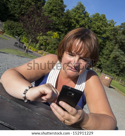 mature woman in park texting on mobile phone