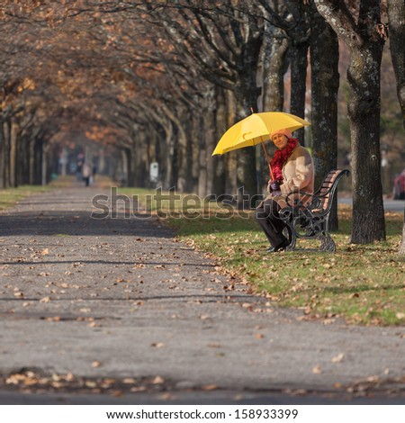 Mature woman in the fall park with yellow umbrella