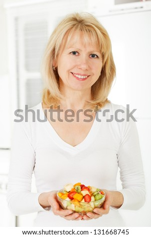 Mature woman in the kitchen with fruit salad in hand