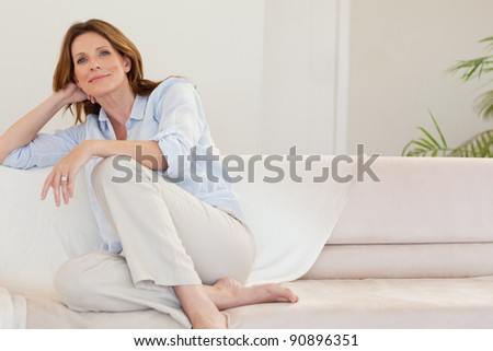 Mature woman in thoughts on the sofa - stock photo