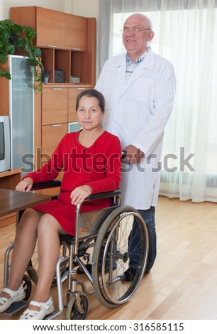 mature woman in   wheelchair and   adult male doctor nearby.