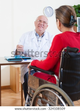 mature woman in   wheelchair and   adult male doctor nearby.  - stock photo